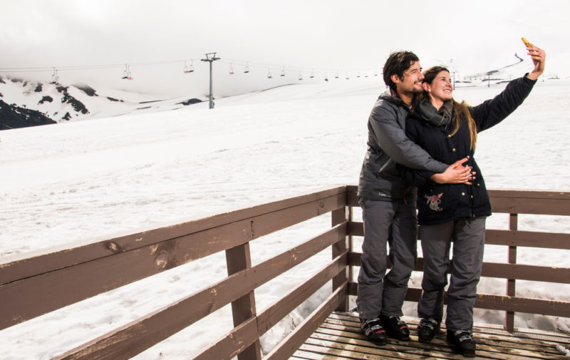 Imagen de una pareja románticamente abrazados tomandose fotografías en Valle Nevado