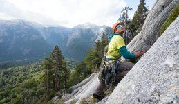 Imagen de un deportista escalando uno de los cerros de Cochamó, donde se ve de fondo la naturaleza prístina de Chile