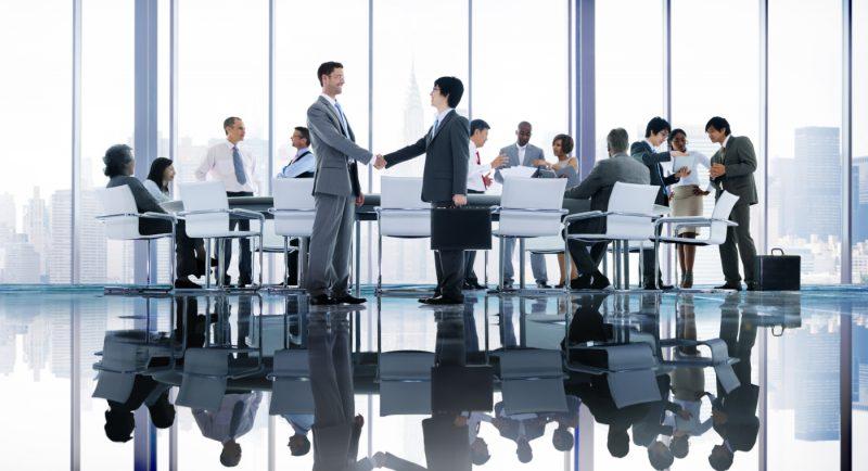 Imagen de un grupo de personas realizando una reunión de trabajo en una oficina vidriada que muestra en primer plano a dos hombres dándose la mano en señal de cerrar un trato