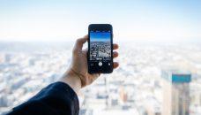 Imagen que muestra la mano de un hombre sosteniendo un smartphone con una aplicación de turismo