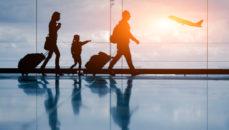 Imagen de una familia de tres personas caminanado por el aeropuerto con aviones despegando de fondo