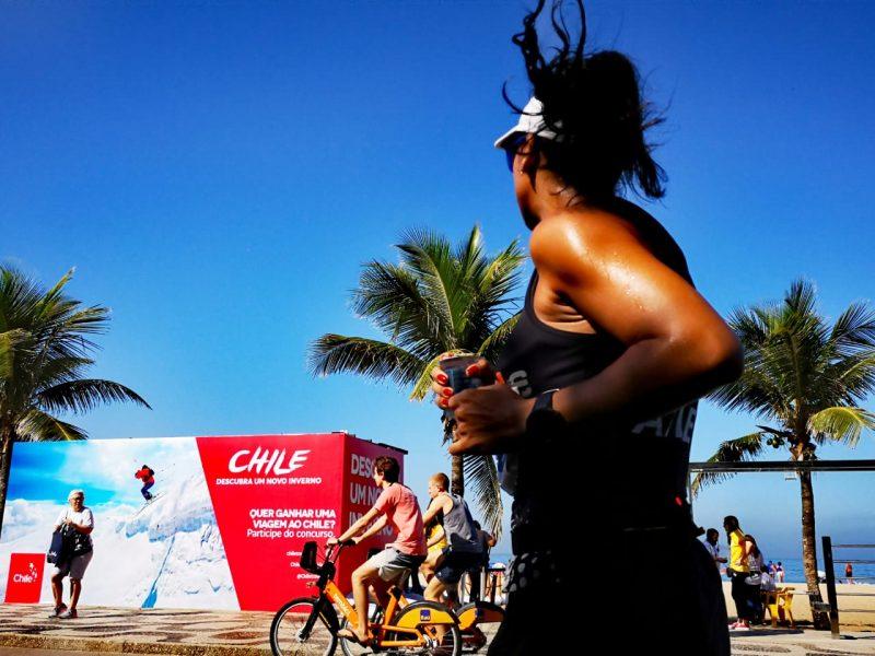Imagen de una mujer corriendo por las playas de Brasil y de fondo se ve el logo y la promoción de Chile