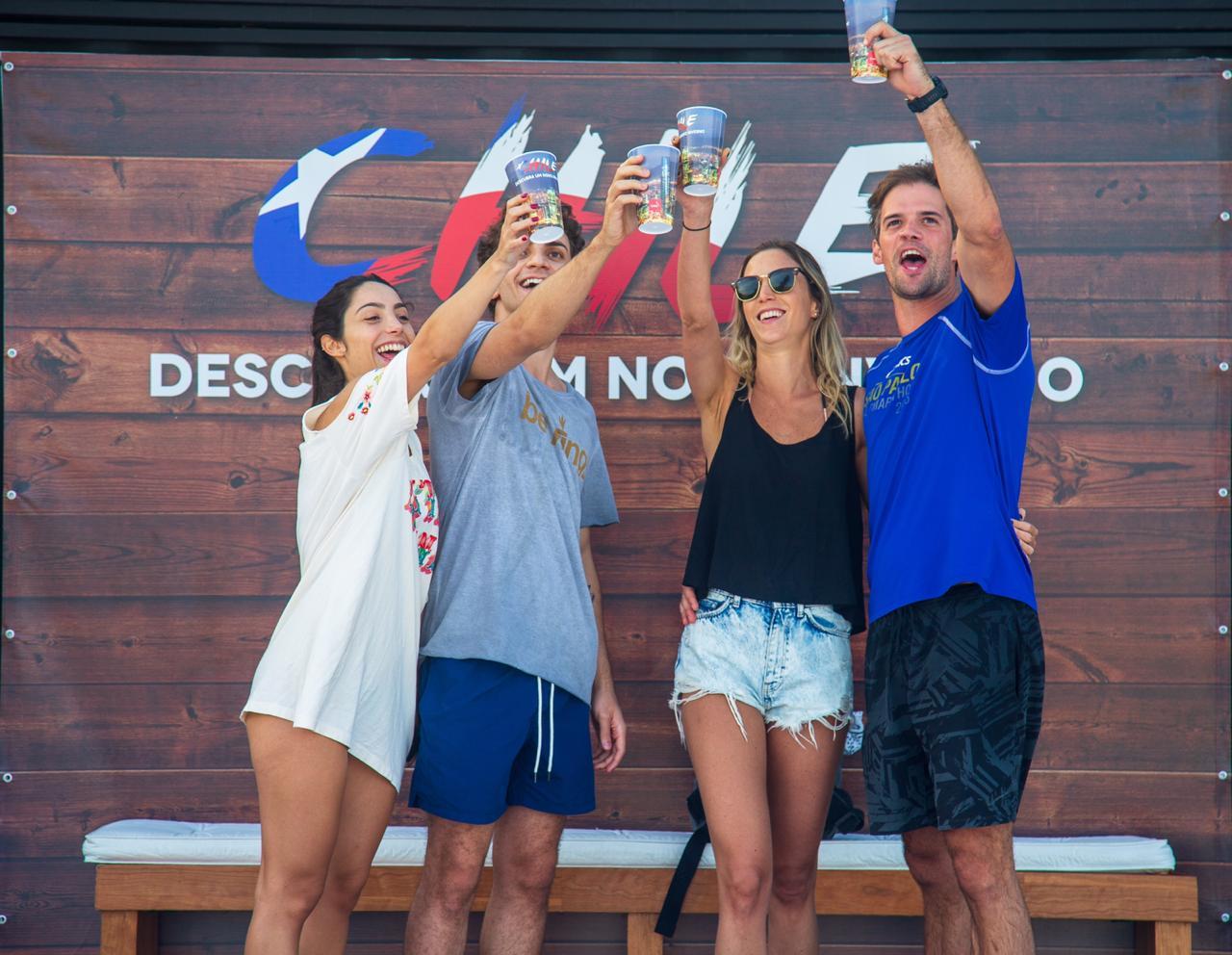 Grupo de amigos en plena playa de Brasil brindando por Chile y sus vinos
