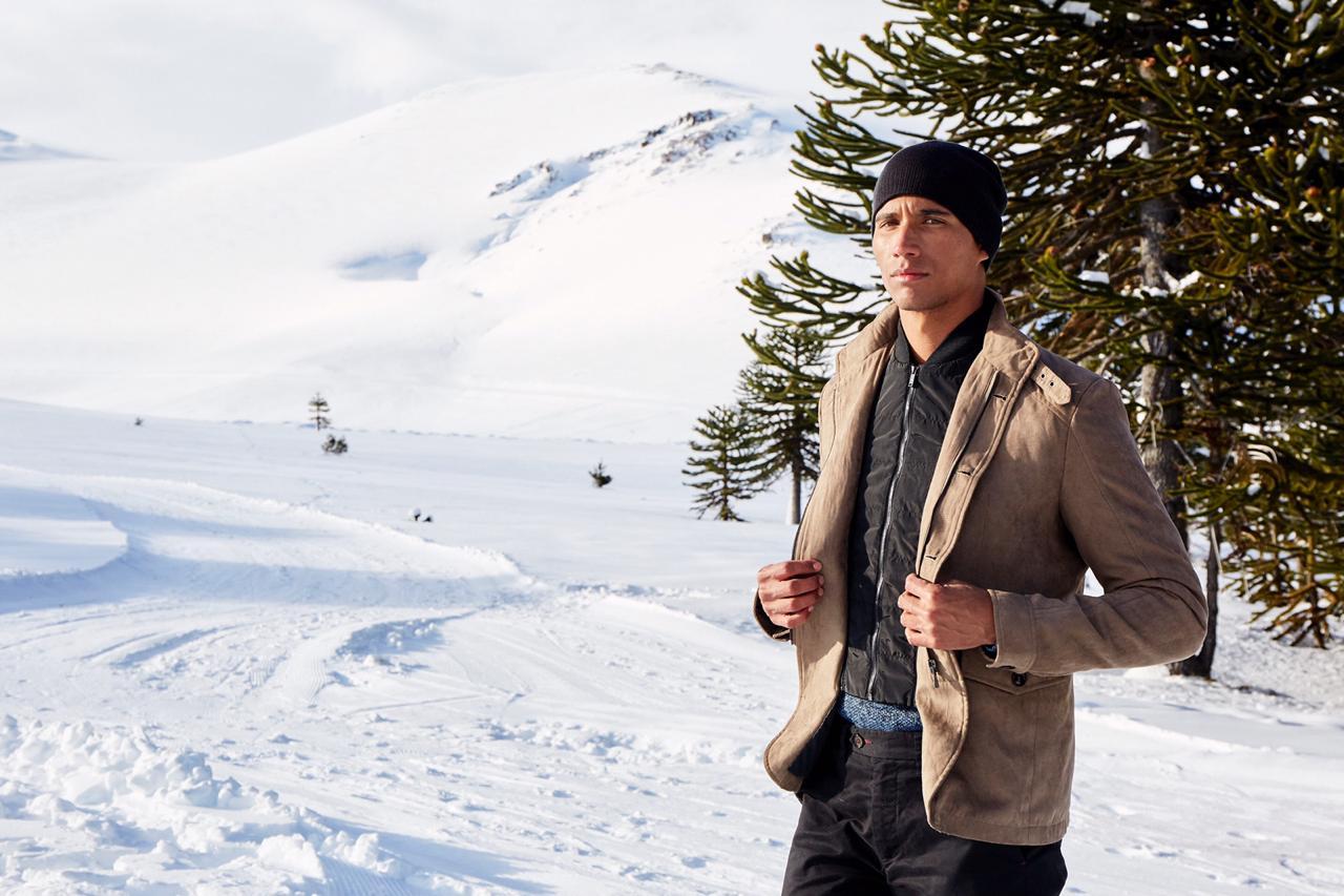 Imagen de un hombre modelanod ropa de invierno en meio de los bosques nevados de Malalcahuello