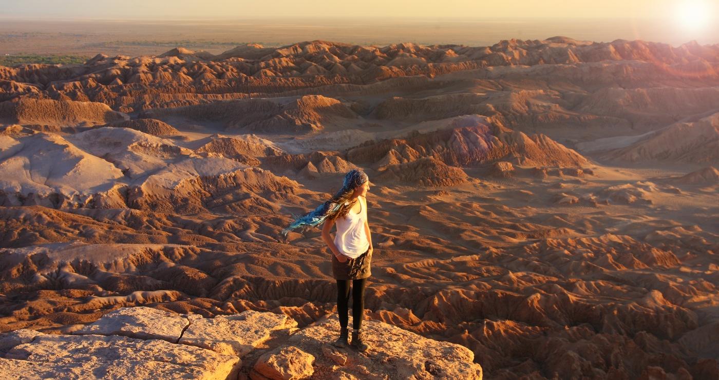 Imagen de una turista disfrutando la vista del Desierto de tacm, en medio del Valle de la Luna