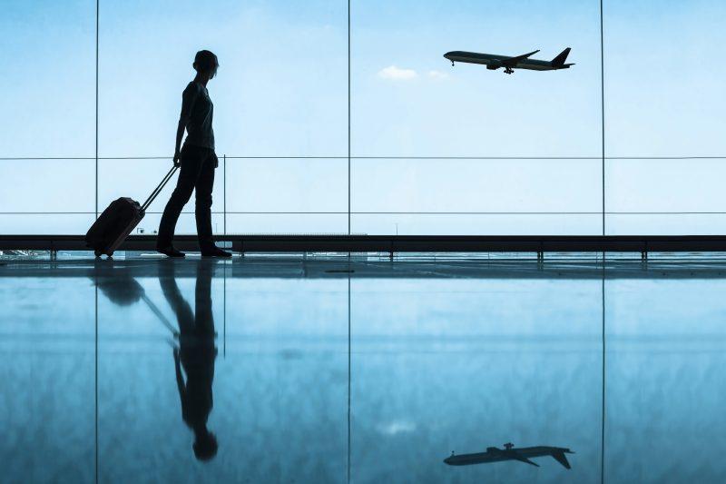 Mujer en sala espera aeropuerto con su maleta